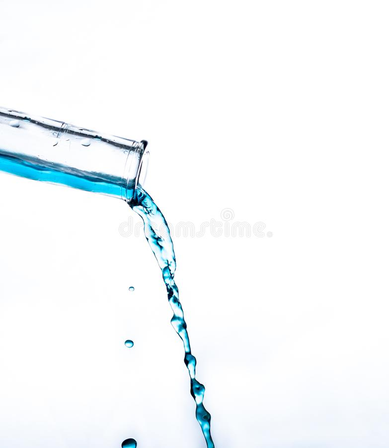 Water pouring out of a glass bottle stock image