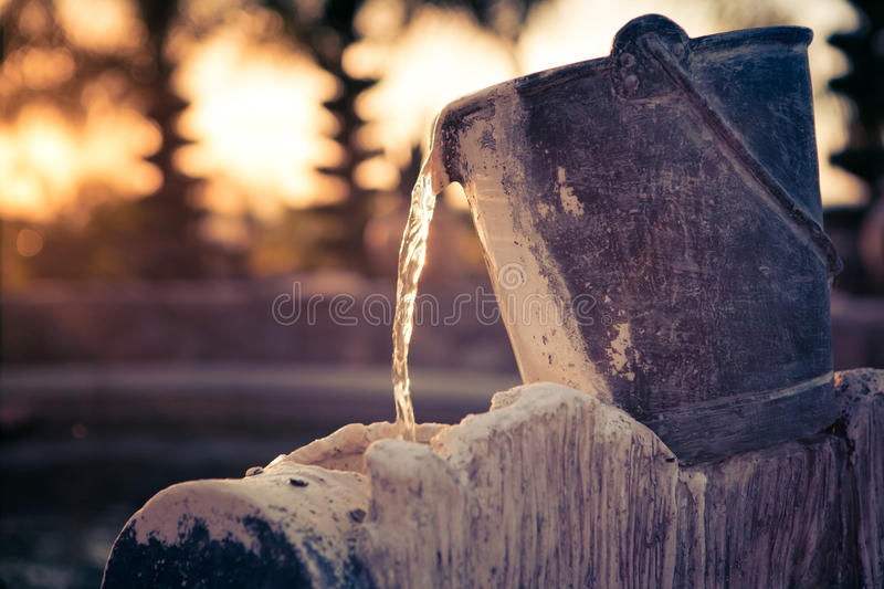 Water pouring out of a vintage bucket. Stone made vintage art bucket as a fountain captured in sunset time stock photo