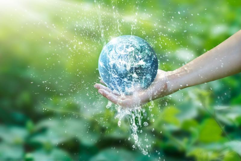 Water pouring on planet earth placed on human hand royalty free stock photos