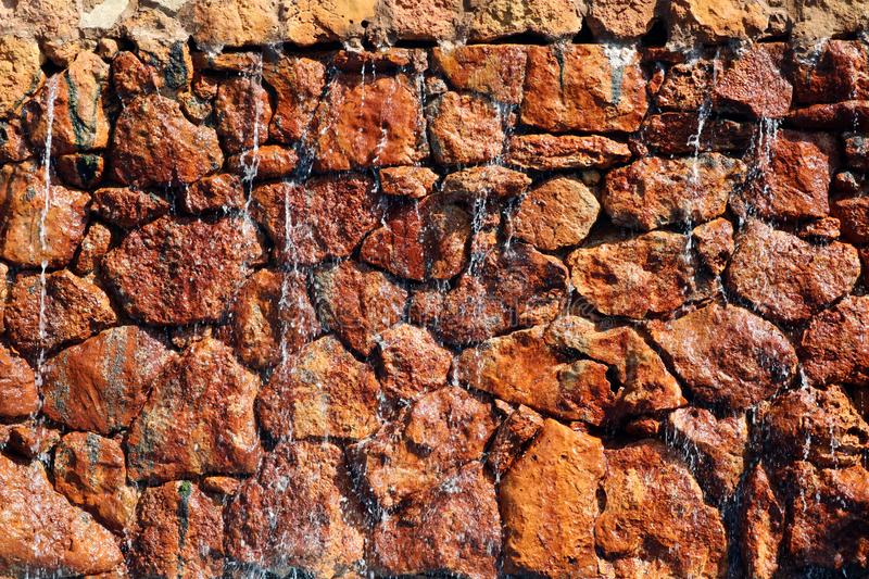 Water pours over the red stones on the wall. For design royalty free stock images