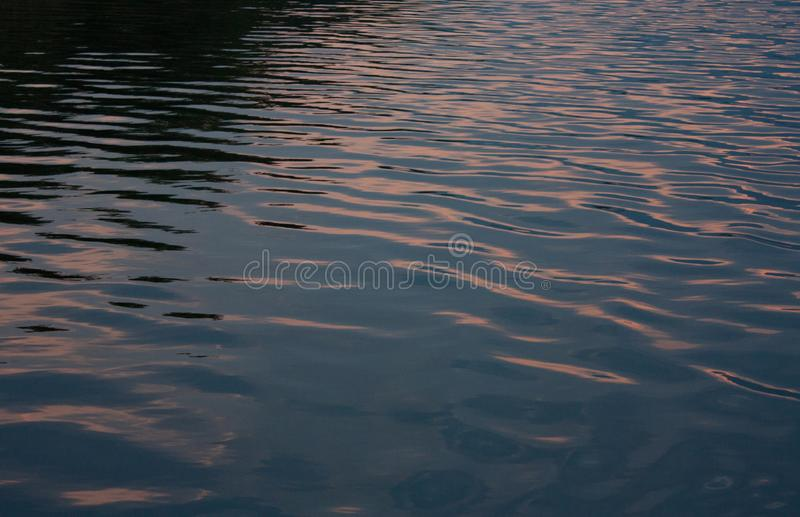 Water of the Preaek Tuek Chhu River near Kampot in Cambodia reflecting sunset. Water of the Preaek Tuek Chhu River near Kampot in Cambodia reflecting pink sunset stock photography