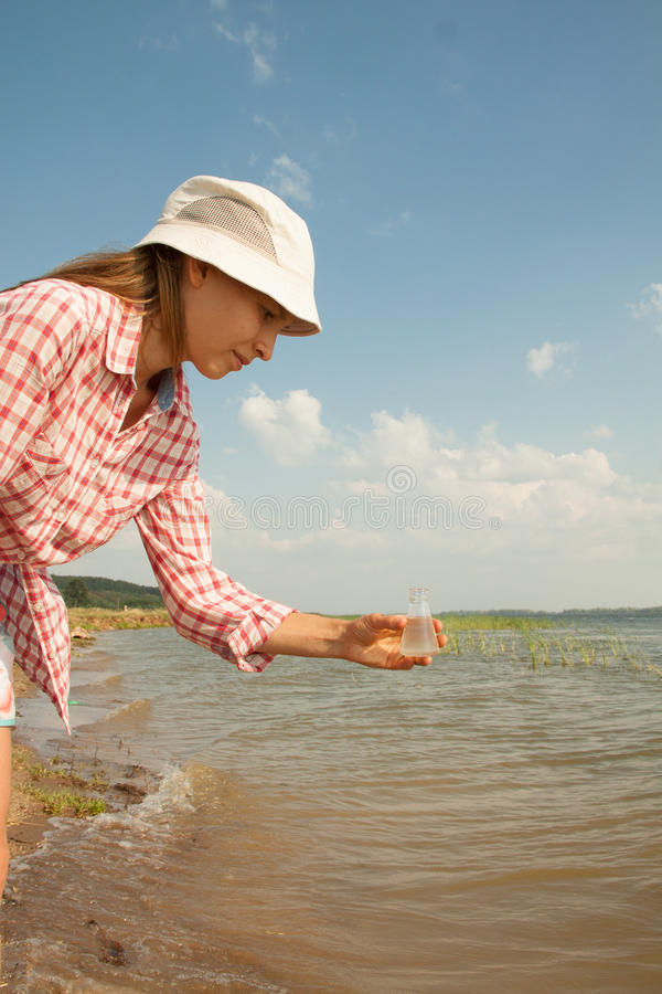 Water Purity Test. Woman holding chemical flask with water, lake or river in the background. stock image