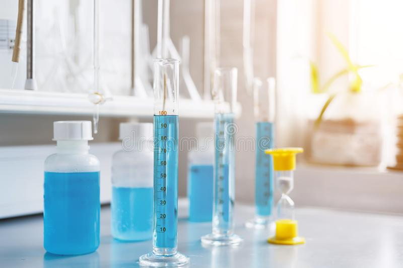 Water quality analysis in a chemical laboratory, a device for measuring pH using equipment made of glass, yellow hourglass. Analysis of water quality in a royalty free stock photography