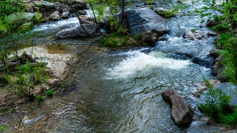 Running Water In The Woods. Water rapids erode boulders in a forest in a state park stock photo