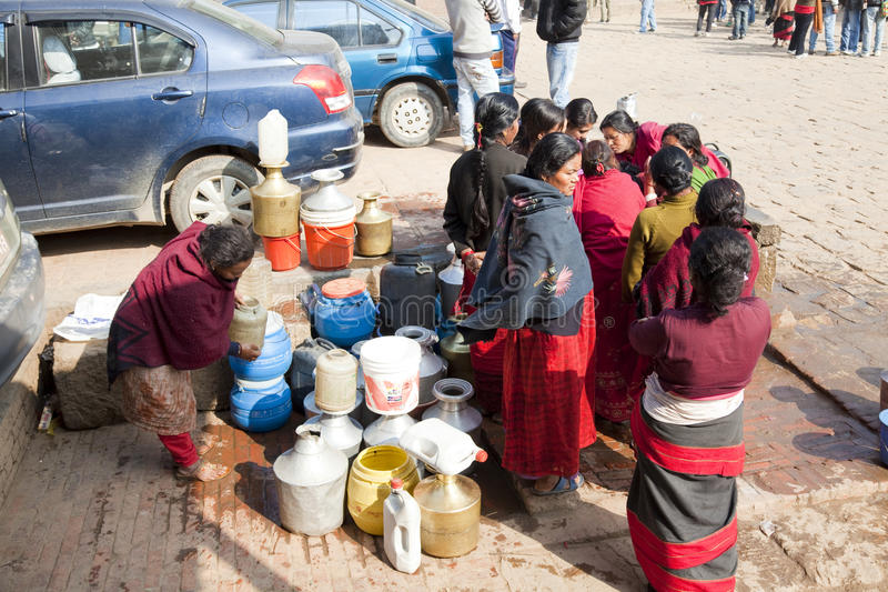 Water Rationing Scene, Bhaktapur, Nepal. Image of women collecting water from a street side public pipe during a water rationing period at the ancient 9th royalty free stock image