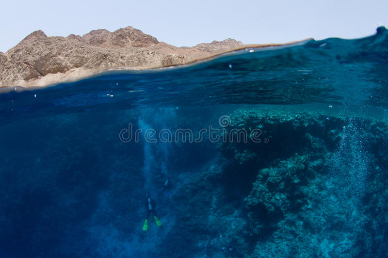 Water with reef and desert mountains. Half half shot of the Blue Hole in Dahab, South Sinai, Egypt stock photos
