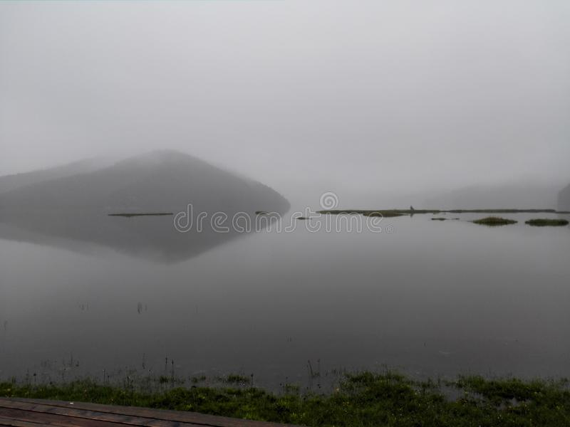 The water is reflected in patches of wetland that have been cut up by the lake,a heavy fog filled the sky royalty free stock photos