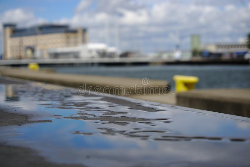 Water reflection in harbour. Water reflecting the sky on a concrete surface in a summers day in the harbour. Developed using darktable 2.6.2 stock photography