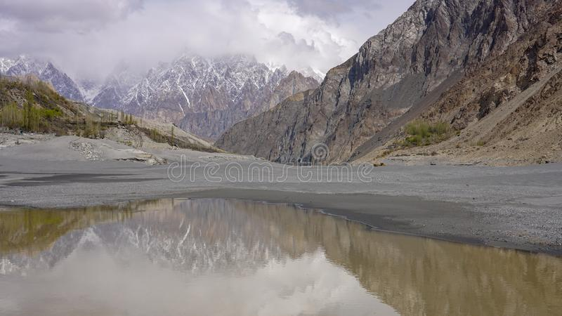 Water reflection of Karakoram mountain ranges. On a small water swamp in Hunza river, Gilgit, Balistan, Pakistan royalty free stock photos