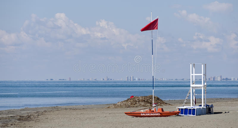 Water rescue with boat and outlook tower. At the beach of Grado with skyline of Lignano in the back, Italy royalty free stock photography