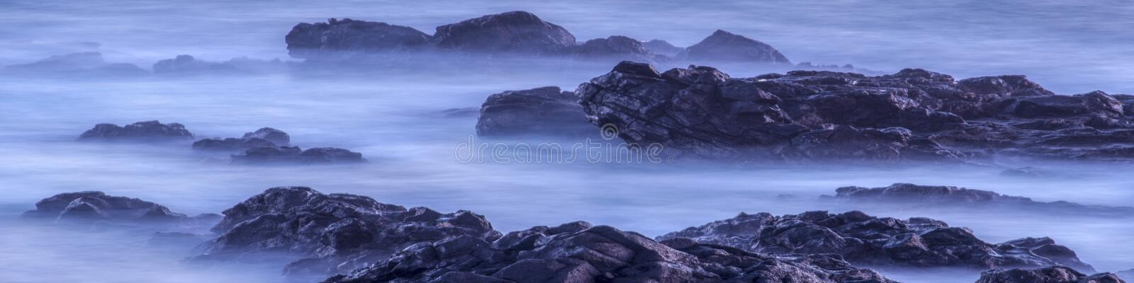 Water with rock nature photo with long exposure fog effect.Panorama or banner abstract color ocean background stock image