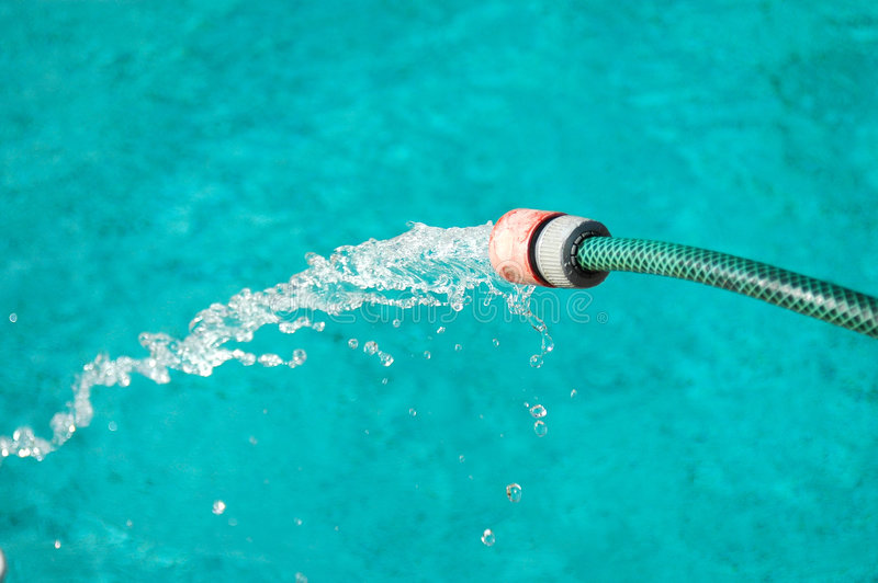 Water running. A pipe with running water into a blue swimming-pool royalty free stock photo
