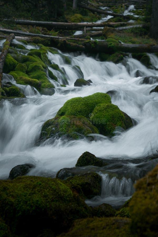 Water running around rock stock image