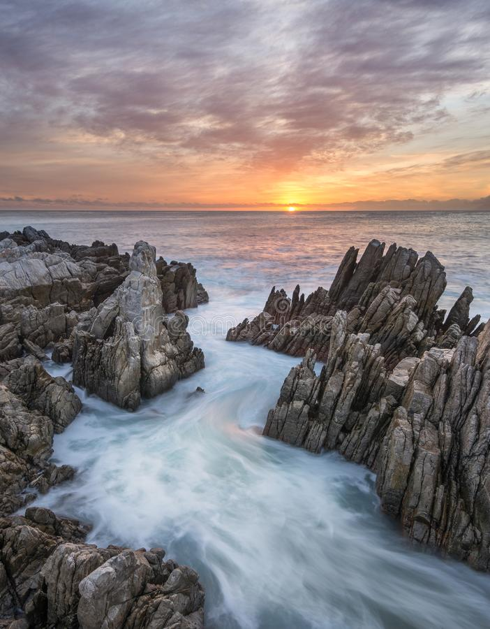 Water rushes in from the ocean during spectacular sunset. Water rushes out between rocks in a zigzag pattern at sunset on the coast of De Kelders - South Africa stock image