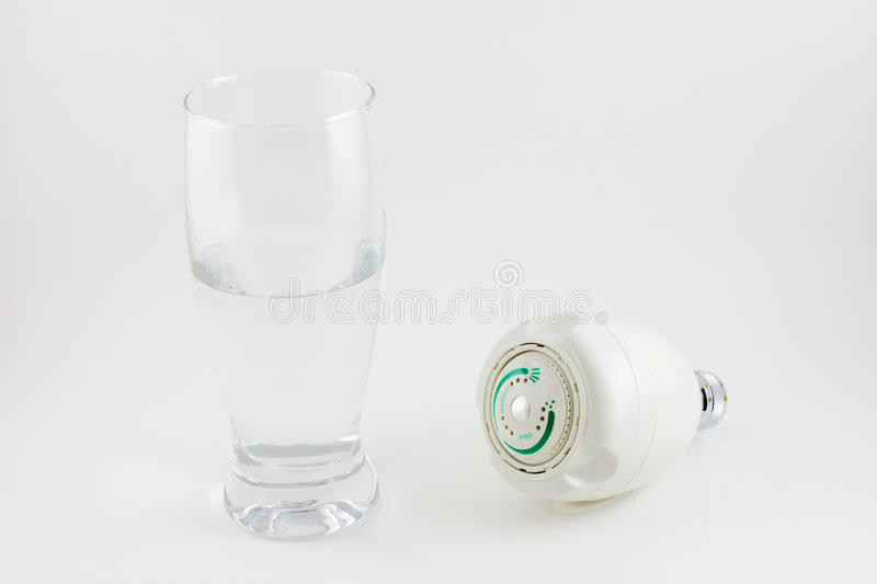 Water Saving. Concept - A half glass of water and an adjustable spray and massage shower head stock images