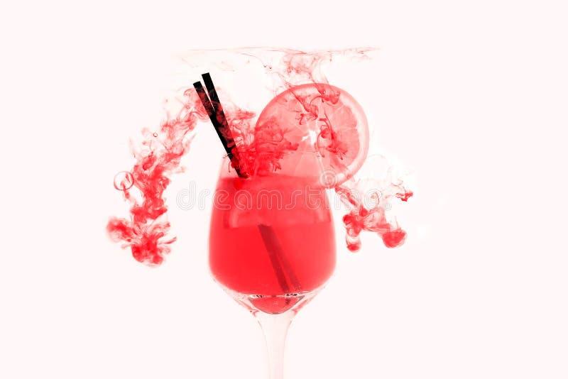 Water schiet het rode roze wit als achtergrond binnen onder verven acrylrook het jus d'orange van het cocktailglas weg stock foto
