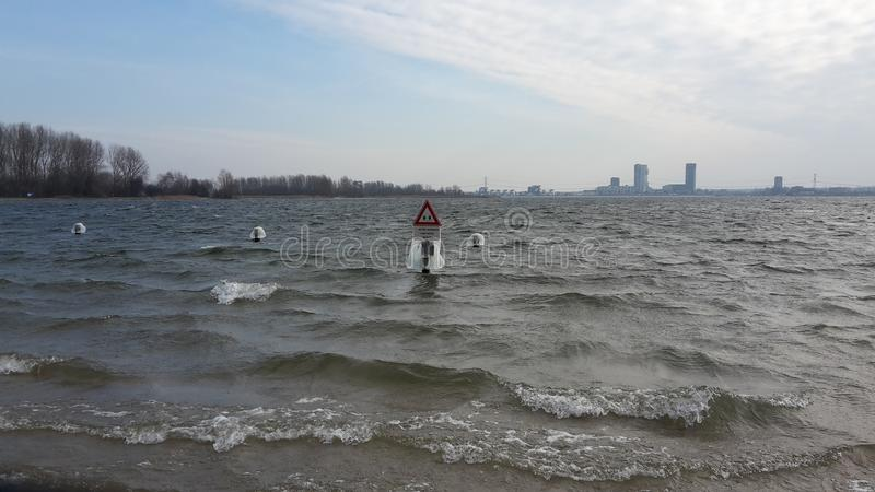 Water on sign and posts is frozen on the Zevenhuizerplas in the stock image