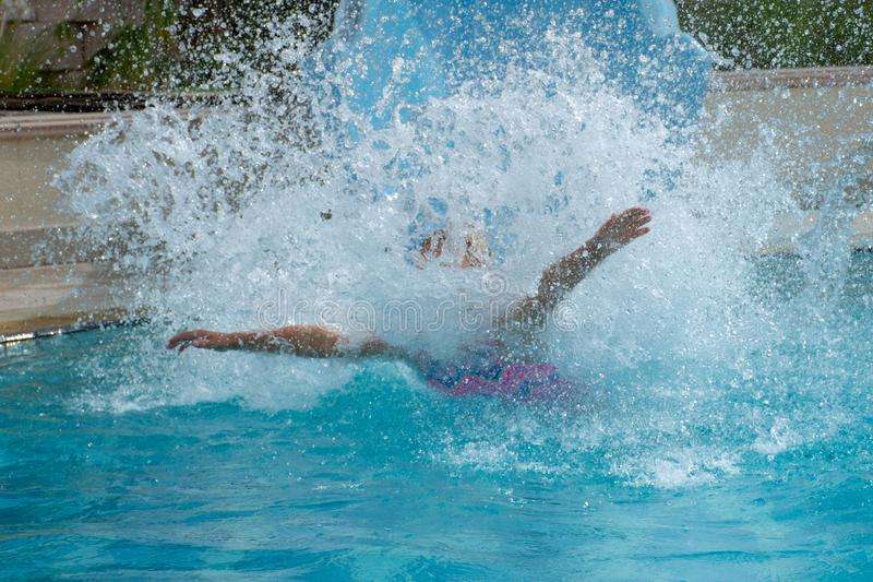 Water slide fun in the swimming pool in the summer crashing into the water making a big splash. Young girl going down water slide having fun in the swimming pool royalty free stock photos