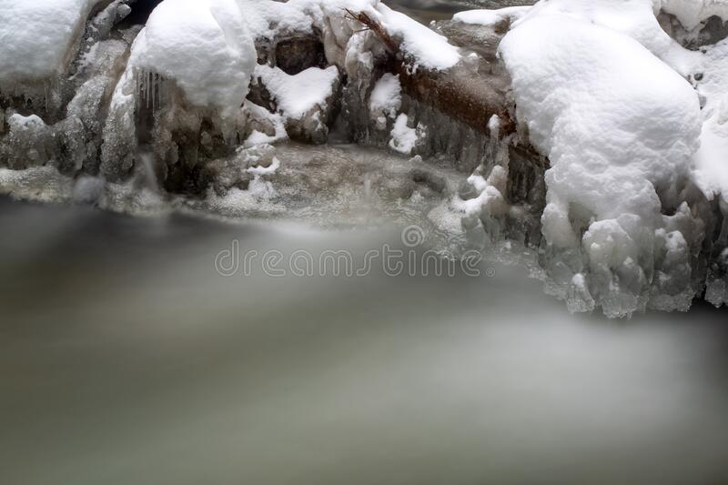Water and snow in mountains - slow motion picture. COld Water and snow in mountains - slow motion picture stock image