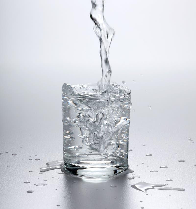 Water som flödar in i fullt exponeringsglas arkivfoton