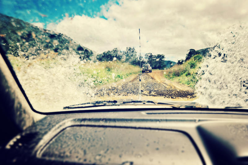 Water splash. A 4x4 makes a splash as it crosses a creek, view from inside the vehicle royalty free stock images