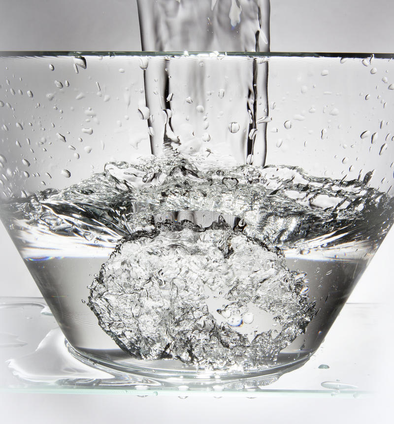 Water splash in a bowl. A water splash in a glass bowl filled with water, taken in studio stock photography