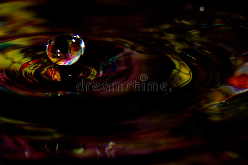 Water splash in color with a drop of water. Flying from above royalty free stock images
