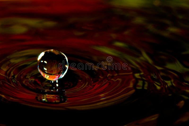 Water splash in color with a drop of water stock photo