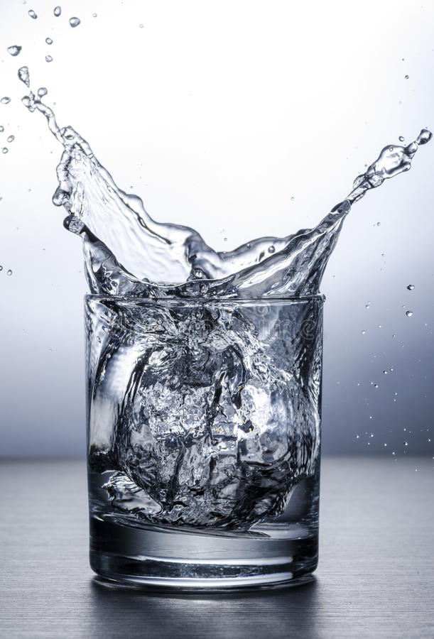 Water Splash. A water splash made by throwing an ice cube into the glass from a height stock image