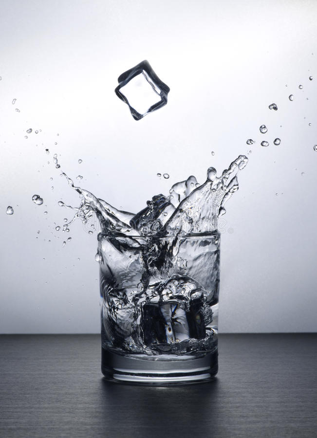 Water Splash. A water splash made by throwing an ice cube into the glass from a height. An ice cube was also shot mid air stock photo