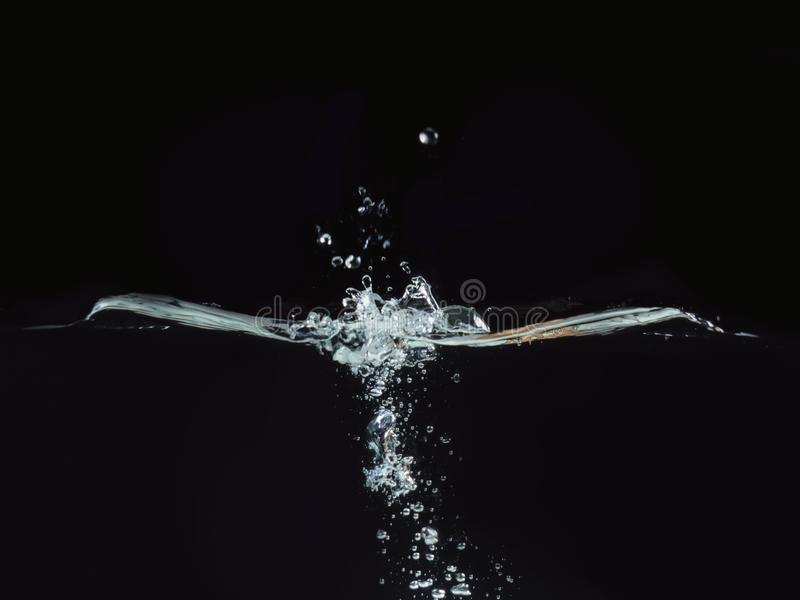 Water splash, rippling surface and small water bubbles isolated on black background, close up view. Perfect for. Compositing into your shots. Ready to use royalty free stock photography