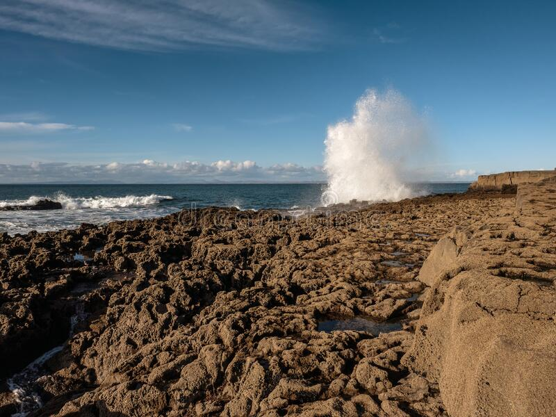 Water splash on a sunny day, Wave hits stone coast line, West of Ireland. Blue clear sky, Sumner time.  stock photos
