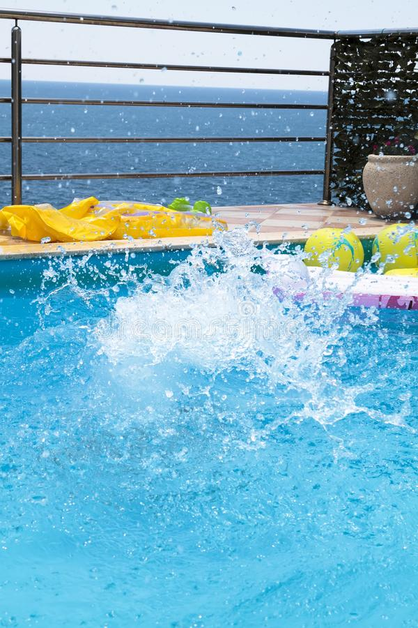 Water splashes after the baby boy jump into the pool. Blue, fun, background, summer, swimming, wet, slide, girl, kid, splashing, child, vacation, park, happy royalty free stock photo