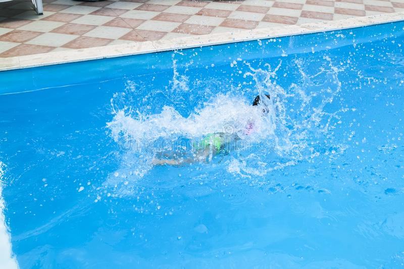Water splashes after the baby& x27;s jump into the pool. Blue, fun, background, summer, swimming, wet, slide, girl, kid, splashing, child, vacation, park royalty free stock photos