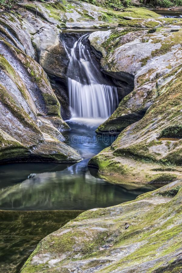 The Upper Falls at Boch Hollow - Hocking Hills, Ohio. Water splashes down a chute carved by water into moss-covered rock at Upper Robinson Falls at Boch Hollow stock images