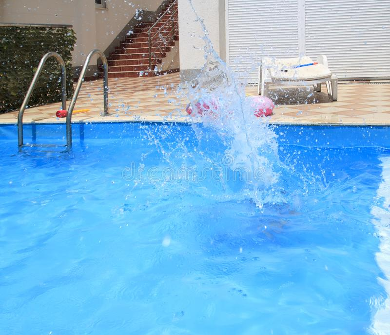 water splashes after the kid& x27;s jump into the pool stock photos