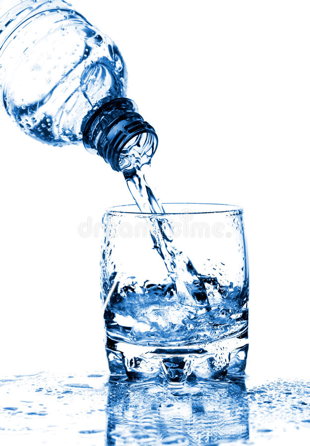 Water splashing from bottle into glass