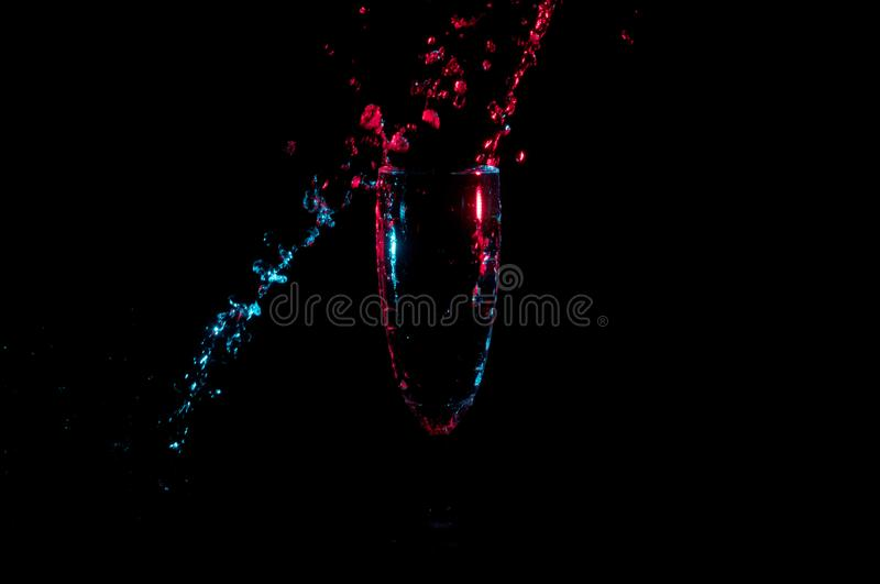 Water splashing in a diagonal line around a champagne flute in red and blue light isolated on a black background stock photo
