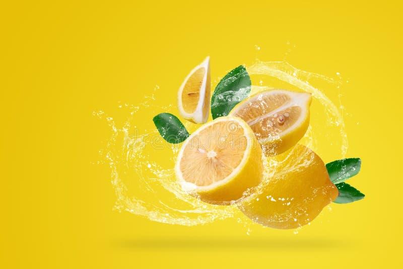 Water Splashing en gele citroenvruchten op een gele achtergrond royalty-vrije stock fotografie