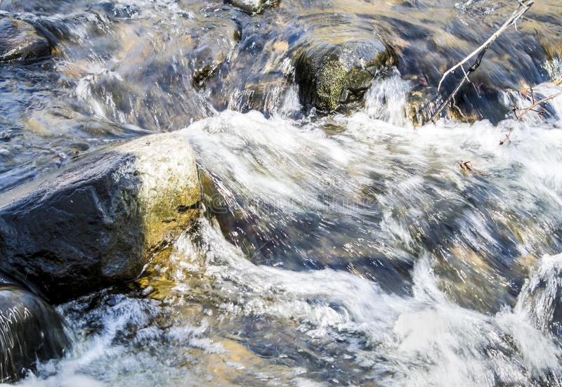 Water Splashing Over Rocks. In a fast moving brook stock image