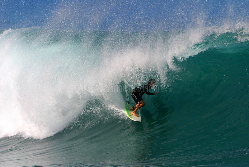 Water Sport Surfer Surfing at Pipeline. A surfer riding deep in the tube of a wave while surfing in Hawaii stock image