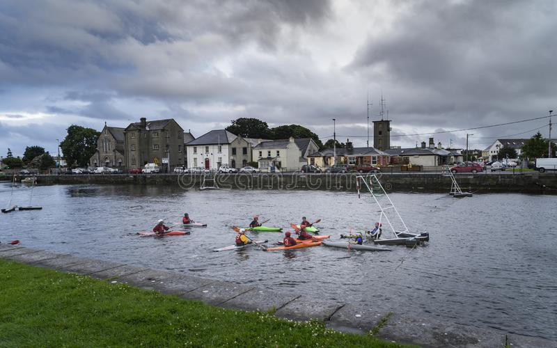 Water sports in Galway in Ireland. Young people practicing water sports in Galway in Ireland with a very cloudy sky royalty free stock photo