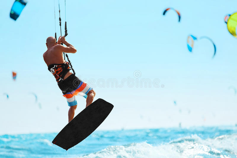 Water Sports. Kiteboarding, Kitesurfing In Ocean. Extreme Sport. Water Sports. Kiteboarding, Kitesurfing. Kiter Jumping On Waves In Ocean. Extreme Sport Action stock photos