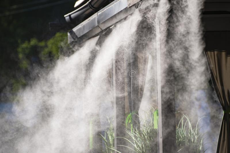 Water spray system for cooling in a public cafe at the boiling hot summer days stock image