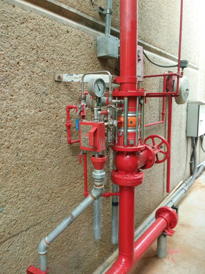 Water sprinkler and fire alarm system. A row of red color fire fighting water supply pipeline system royalty free stock photo