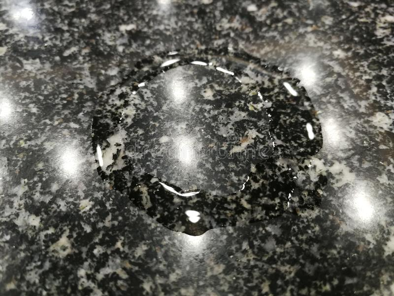 Water stain on marble surface background. Black, white, monochrome, glass, liquid stock photo