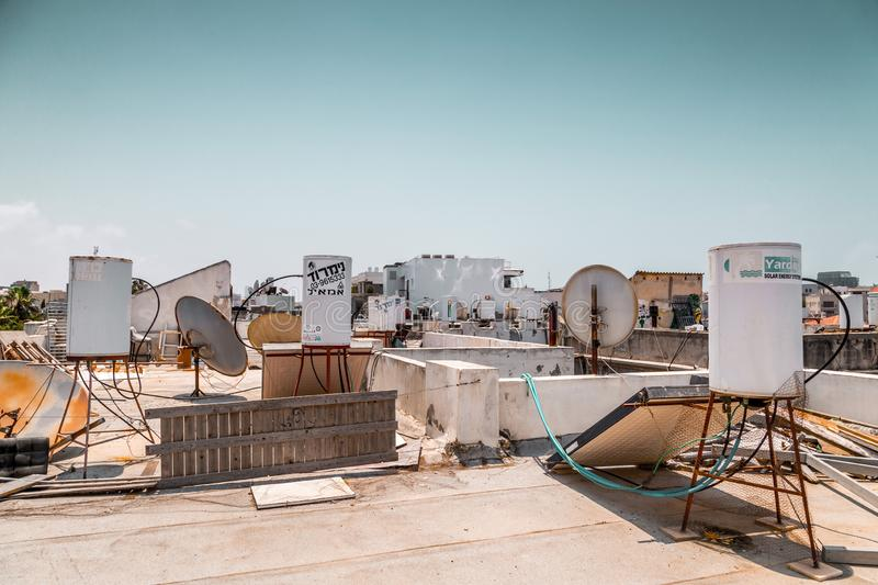 Water storage tanks, solar energy panels and satelites. Jaffa, Israel - June 12, 2019: Water storage tanks, solar energy panels and satelites on the roofs of stock photo