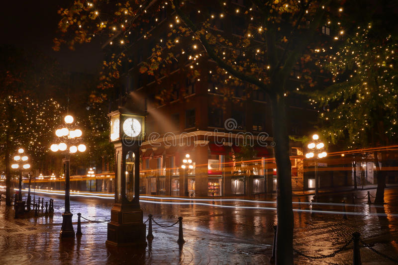 Water Street Night, Gastown, Vancouver. Reflections on the wet street during a rainy night in Vancouver's touristy Gastown district at the steam clock. The stock image