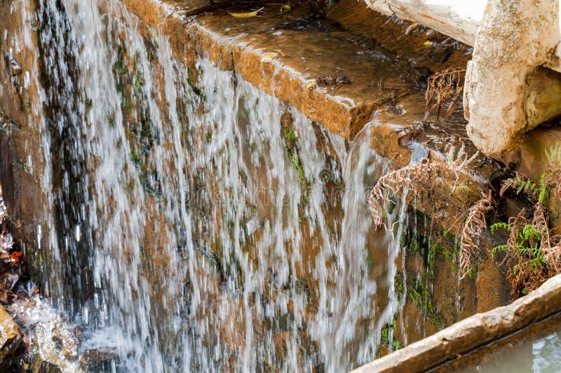 Water stromen die over vlotte rots draperen stock afbeeldingen