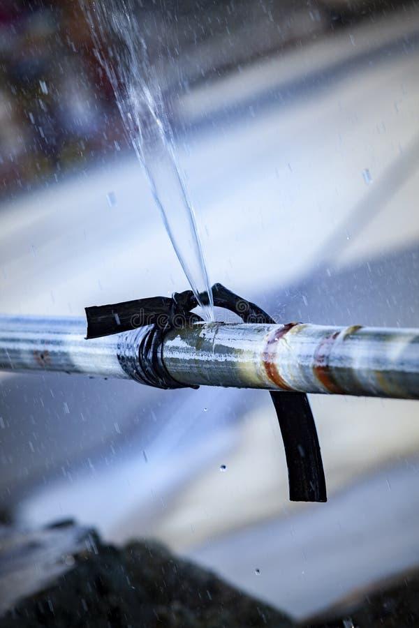 Water stromend verlies van de oude lijn van de metaalpijp stock foto